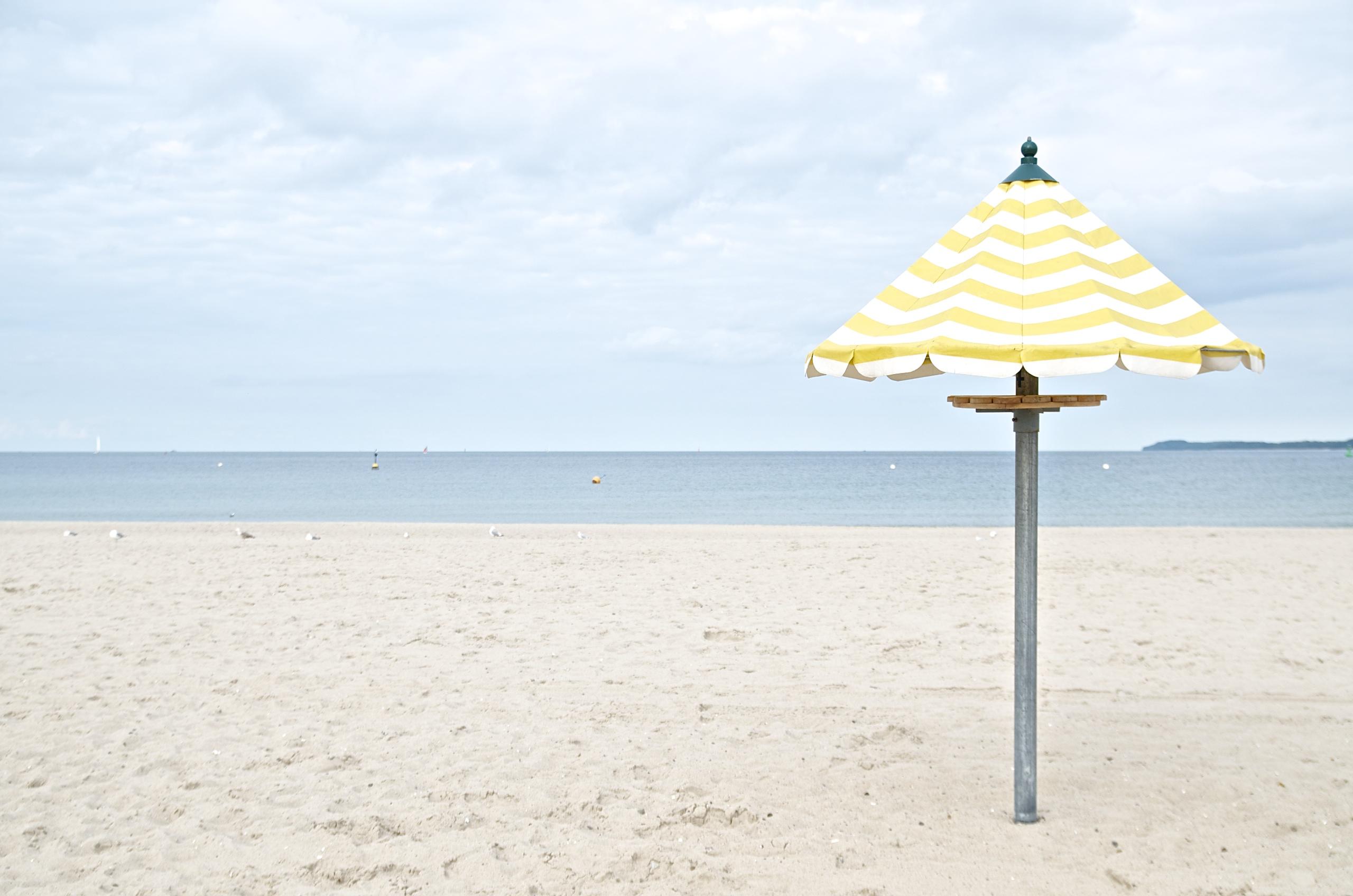 (K)Ein Tag am Meer,gelb-weiß gestreifter Sonnenschirm am Strand in Travemünde, Himmel, Meer
