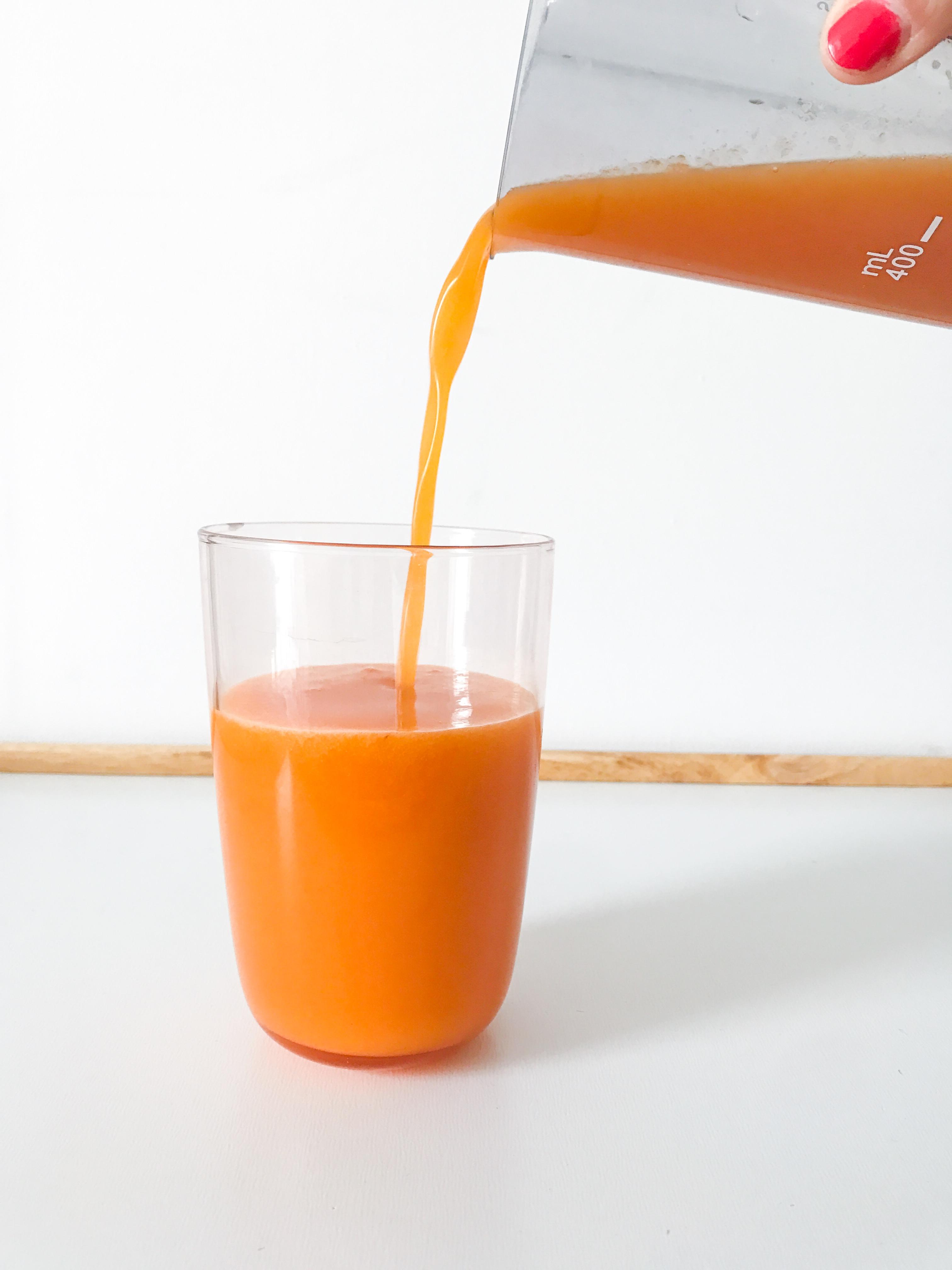 Frisch gepresster Mango-Ananas-Möhren-Nektarinen-Saft aus dem Entsafter