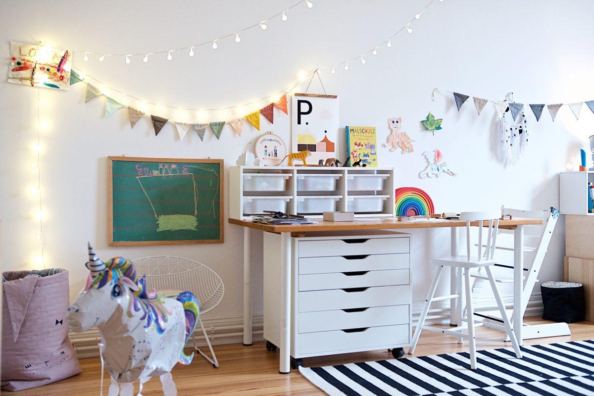 Kreativ-Ecke im Kinderzimmer mit Schreibtisch, Schubladenelement und Lichterketten